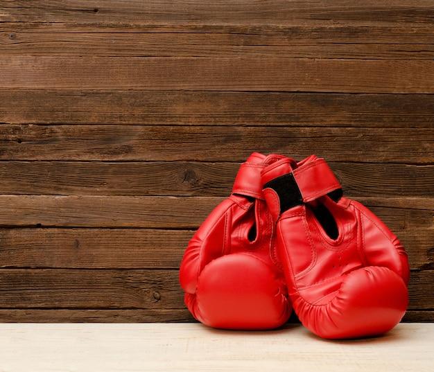Dwa czerwonej bokserskiej rękawiczki na drewnianym brown tle, opróżniają przestrzeń