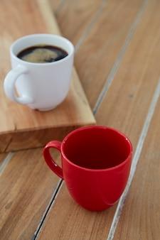 Dwa czerwony i biały kubek kawy na drewniane