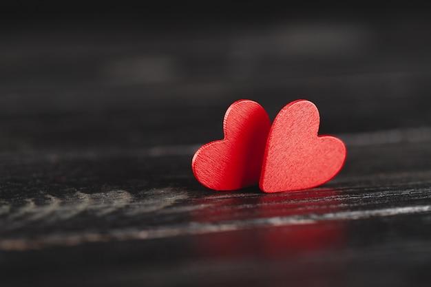 Dwa dekoracyjne serca na ciemnym tle drewnianych
