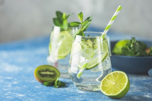 Dwa detoksykacyjne koktajle z wodą lub martini z kiwi, limonką, lodem i miętą