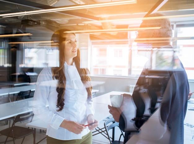 Dwa dojrzała biznesmena i bizneswomanu pozycja za szkłem w biurze