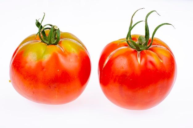 Dwa dojrzałe czerwone pomidory z popękaną skórką. zdjęcie studyjne.