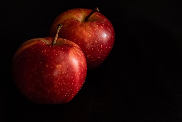 Dwa dojrzałe świeże czerwone jabłka z kroplami wody na błyszczącej skórce na czarnej powierzchni