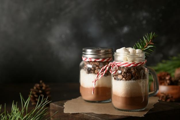 Dwa domowe prezenty świąteczne w słoiku na napój czekoladowy w ciemności. ścieśniać.