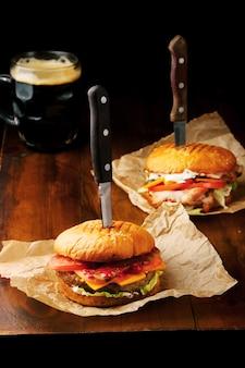 Dwa domowe smaczne hamburgery z dużym kuflem wołowiny, sera, pomidorów i ciemnego piwa na drewnianym stole i czarnym stole.
