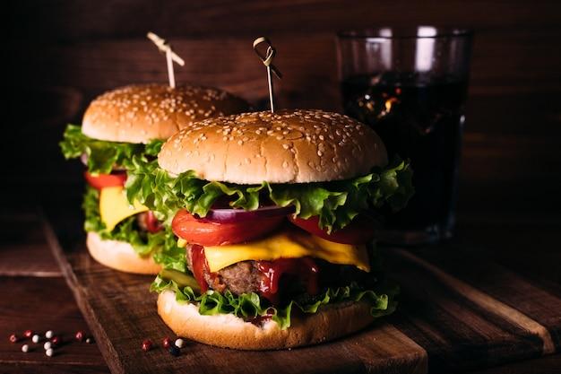 Dwa domowe świeże smaczne hamburgery z sałatą i serem na drewnianym stole w stylu rustykalnym. frytki, pomidory i sos. ciemne tło żywności.