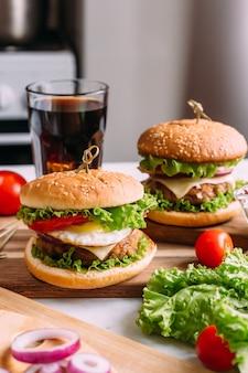 Dwa domowe świeże, smaczne hamburgery z sałatą i serem. składniki na stole. lekkie tło żywności.
