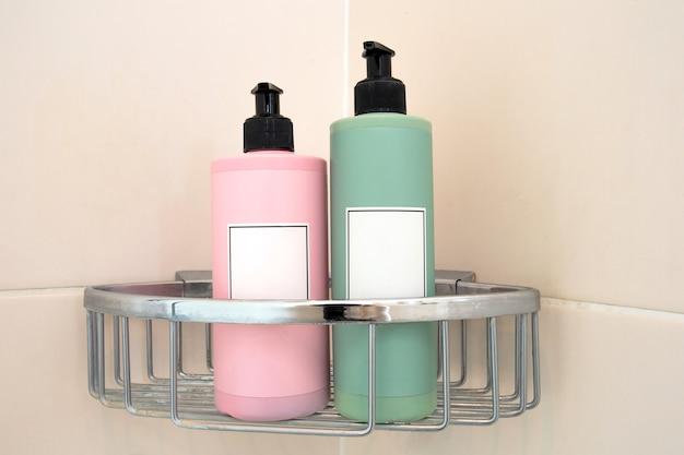 Dwa dozowniki mydła w pastelowych kolorach w kabinie prysznicowej przy ścianie wyłożonej kafelkami