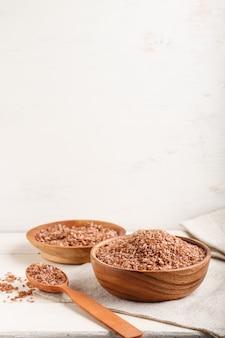 Dwa drewniane miski z nieoszlifowanym brązowym ryżem i drewnianą łyżką na białym tle drewnianych. widok z boku, kopia przestrzeń.