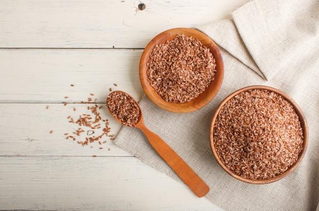 Dwa drewniane miski z nieoszlifowanym brązowym ryżem i drewnianą łyżką na białym tle drewnianych. widok z góry, kopia przestrzeń.
