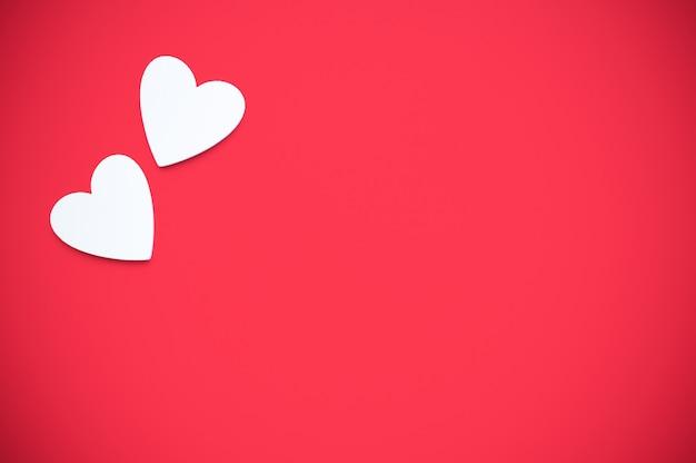 Dwa drewniane serca w rogu na jasnoczerwonym tle papieru