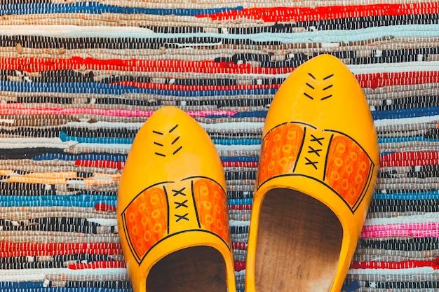 Dwa drewniane stojaki na buty na kolorowej macie