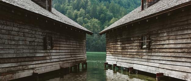 Dwa drewniane szare domy na wodzie w zalesionych alpejskich górach austrii.