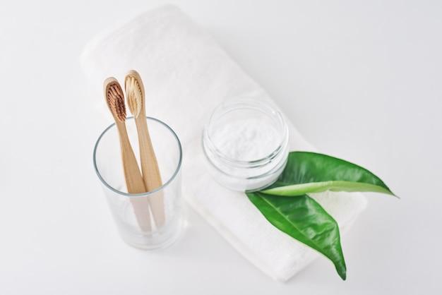 Dwa drewnianej bambusowej ekologicznej szczoteczki do zębów w szkle, sodzie oczyszczonej i ręczniku na białym tle.