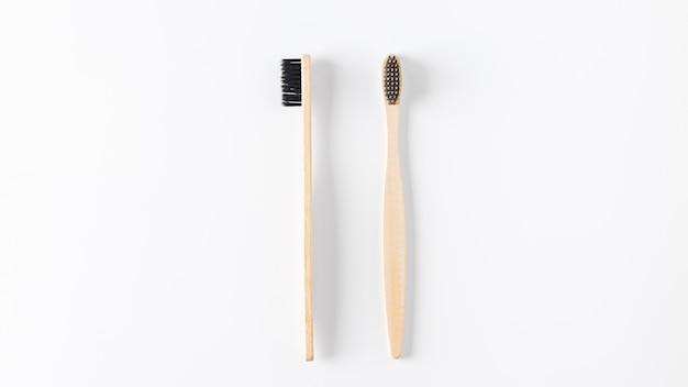 Dwa drewniany toothbrush na białym tle. pojęcie zero odpadów, recykling, świadomość ekologiczna, społeczna odpowiedzialność za środowisko. zmień styl życia