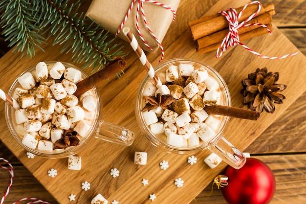 Dwa duże haczyki z napojem czekoladowym lub kakao w noworocznej kompozycji z kulkami, pudełkiem prezentowym i laskami cynamonu. widok z góry.