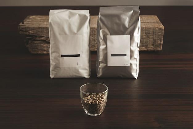 Dwa duże hermetyczne opakowania z pustymi etykietami w pobliżu przezroczystego szkła z surowymi ziarnami kawy