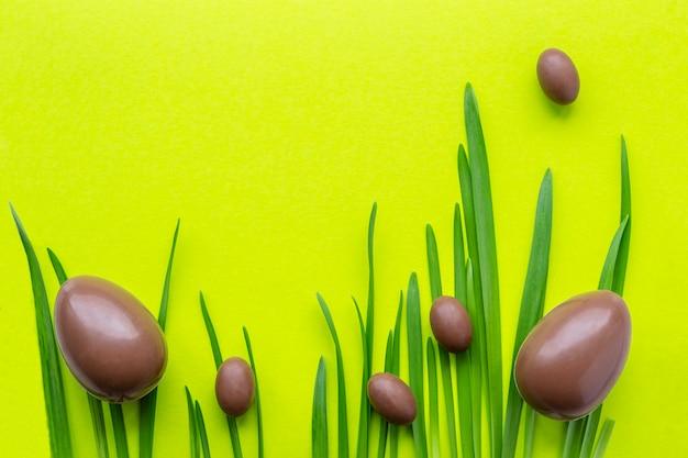 Dwa duże i wiele małych czekoladowych jajek. jajka na trawie i na zielonym żółtym tle. ferie wielkanocne. miejsce na tekst
