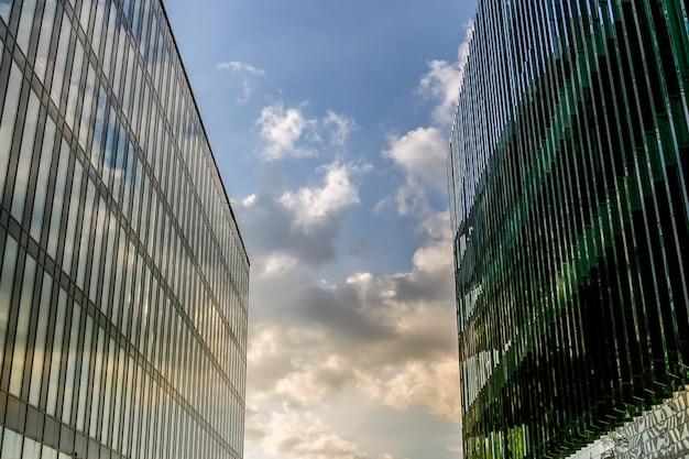 Dwa duże nowoczesne budynki stoją blisko siebie, zamykając niebo.