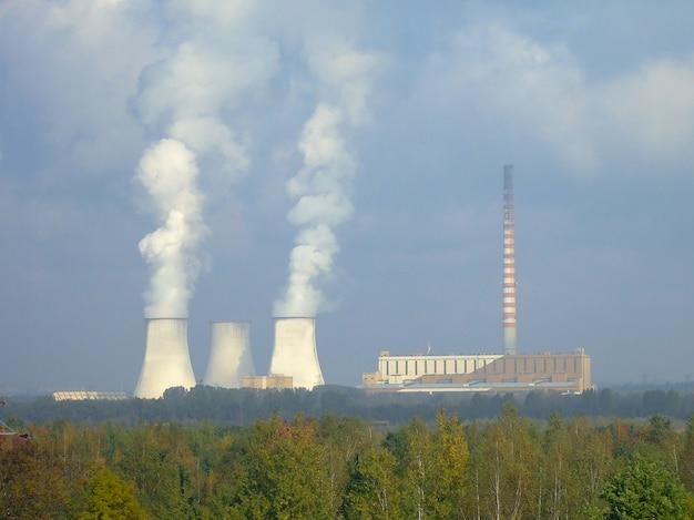 Dwa dymiące kominy elektrowni w tle za zielonym lasem oraz wysoki komin nie dymią. na tle błękitnego nieba