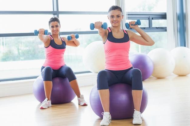Dwa dysponowanej kobiety ćwiczy z dumbbells na sprawności fizycznych piłkach