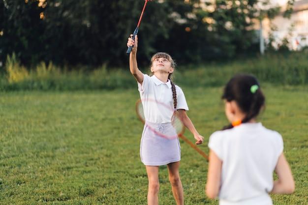 Dwa dziewczyny bawić się badminton w parku