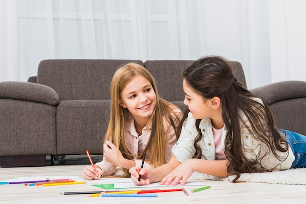 Dwa dziewczyny kłama na dywanowym rysunku z kolorów ołówkami w żywym pokoju