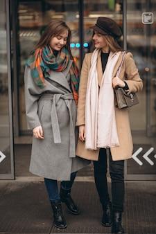 Dwa dziewczyny na zewnątrz centrum handlowego w jesień dniu