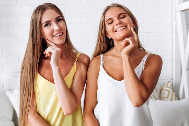 Dwa dziewczyny ono uśmiecha się podczas gdy siedzący na łóżku w domu