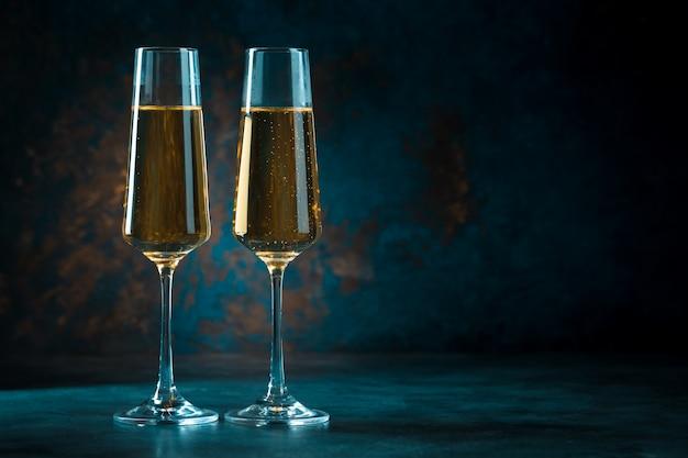 Dwa eleganckie romantyczne kieliszki z błyszczącym złotym szampanem na ciemnym niebieskim tle