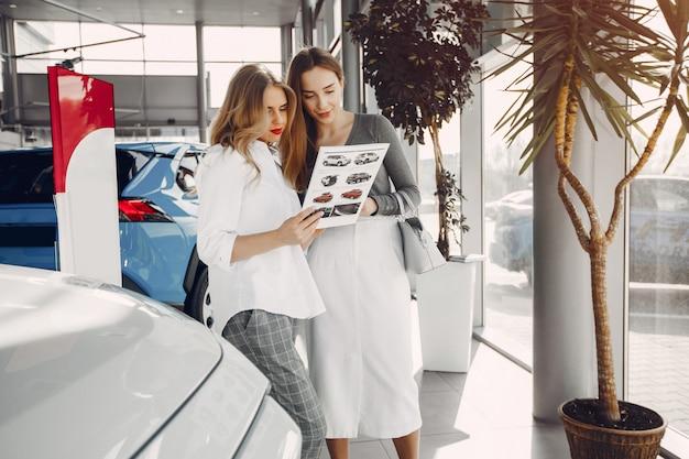 Dwa eleganckiej kobiety w samochodowym salonie