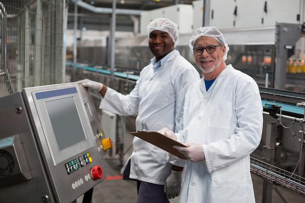 Dwa fabrycznego inżyniera stoi blisko maszyny w fabryce