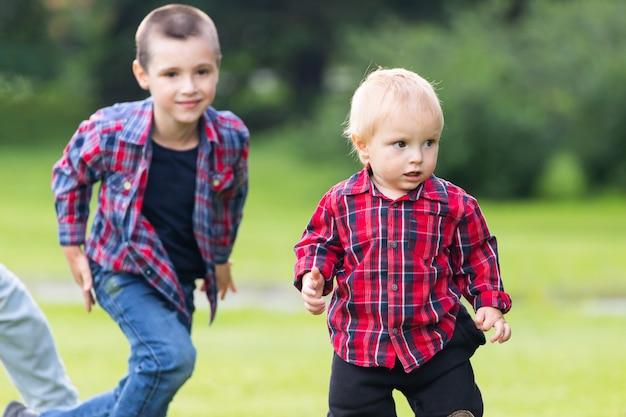 Dwa figlarne dzieci rasy kaukaskiej brata lubią bawić się grając razem w domu przy zielonej trawie