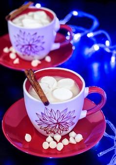 Dwa filiżanek gorąca biała czekolada z marshmallow na czerwień talerzu. czarny i oświetlenie. tradycyjny świąteczny napój.