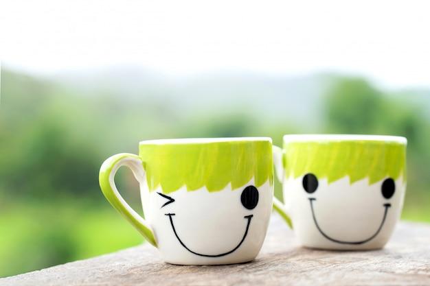Dwa filiżanki kawy na drewnianym tle z naturalną zielenią