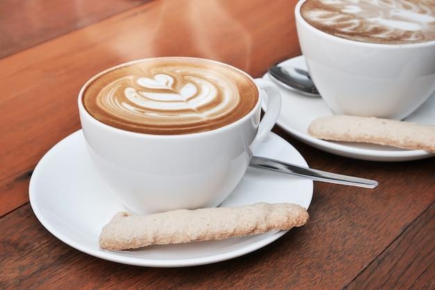 Dwa filiżanki latte sztuki kawa w białej filiżance na drewnianym tle
