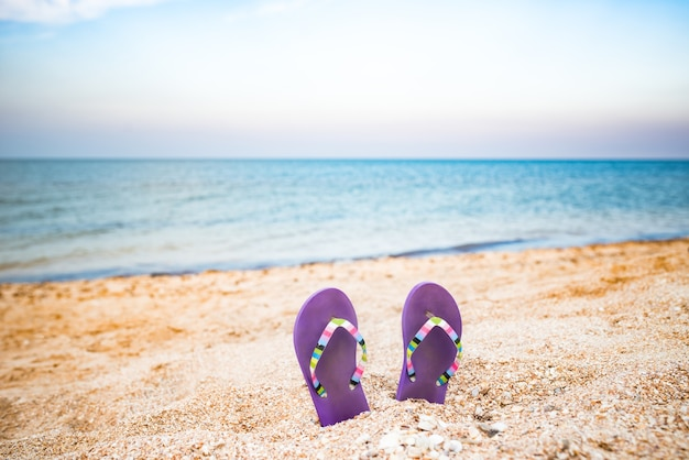Dwa fioletowe kapcie utknęły w piasku na plaży w słoneczny ciepły letni dzień nad błękitnym morzem. pojęcie relaksu i długo wyczekiwanych wakacji. copyspace