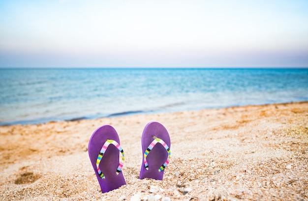 Dwa fioletowe kapcie wbite w piasek na plaży