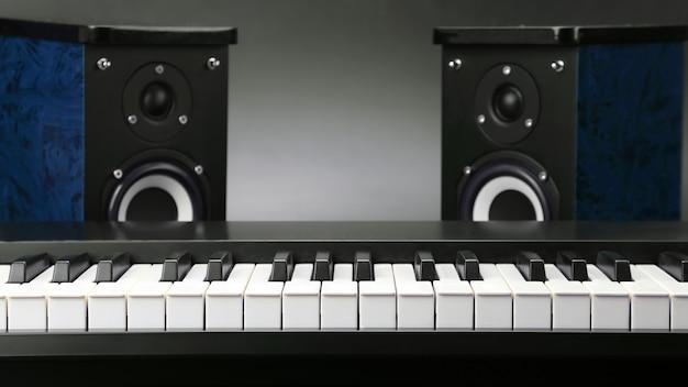 Dwa głośniki stereo audio i zbliżenie klawiszy fortepianu na ciemnym tle. przedmioty do nagrywania