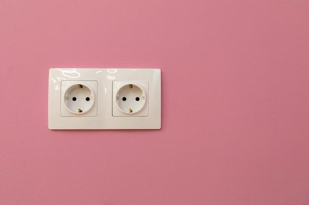 Dwa gniazdka elektryczne na otynkowanej ścianie kopiuj przestrzeń