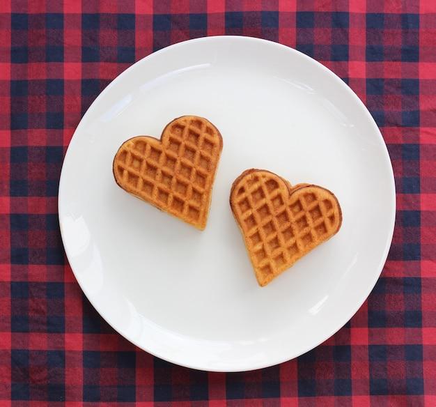 Dwa gofry w kształcie serca na talerzu, widok z góry.