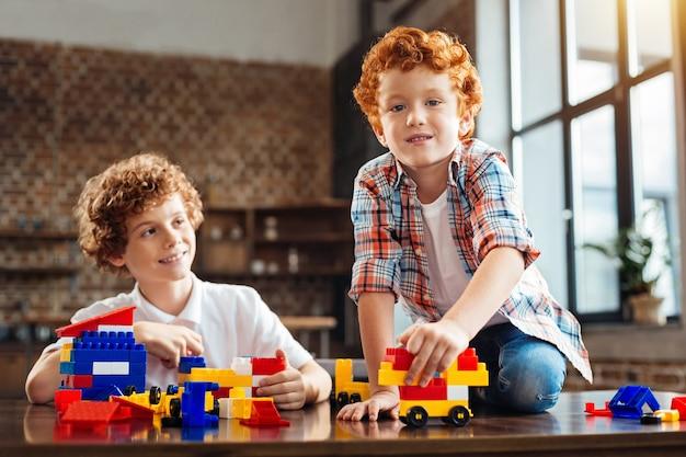 Dwa groszki w strąku. selektywne skupienie się na uroczym chłopcu w koszuli w kratę siedzi na stole i patrząc w kamerę