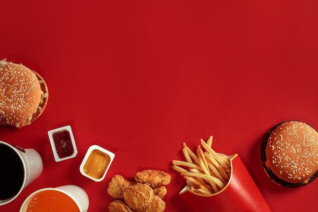 Dwa hamburgery i frytki, sosy i napoje na czerwonym tle fast food widok z góry płasko leżał z...