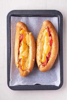 Dwa hot dog fast foodów świeżego sosu serowego kiełbasy na białym tle na blasze
