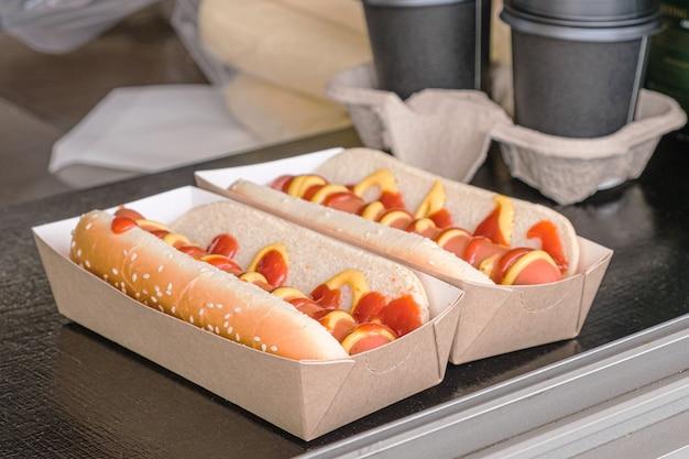 Dwa hot dogi w kartonowym pudełku na ladzie wózka z jedzeniem na wynos.