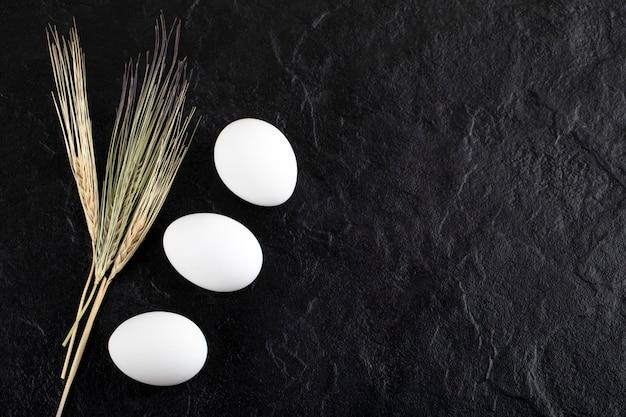 Dwa jajka i uszy koloru białego na czarnej powierzchni.