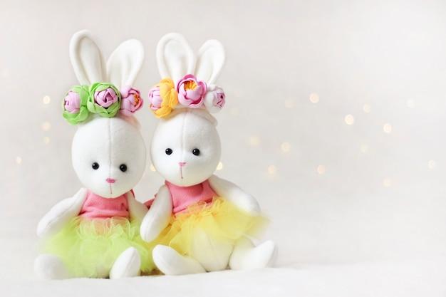 Dwa jasne króliczki. kartka z życzeniami wielkanocnymi i zabawki dla dzieci.