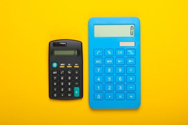 Dwa kalkulatory na żółtym tle. widok z góry.