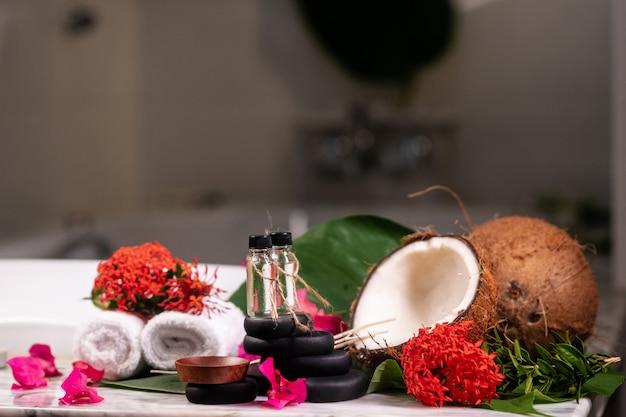 Dwa kamienie aromaterapeutyczne stoją na kamieniach do kamienia terapeutycznego, obok których są poskręcane ręczniki, dwa kokosy i kolorowe kwiaty