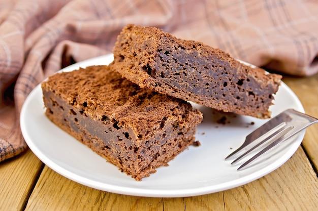 Dwa kawałki ciasta czekoladowego na talerzu, widelcu, serwetce na tle drewnianych desek